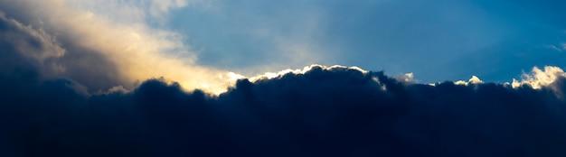 Donkere onweerswolken verlicht door de felle avondzon