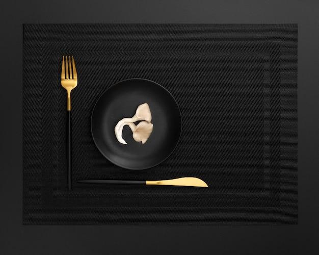Donkere plaat met champignon op een donkere doek met mes en vork