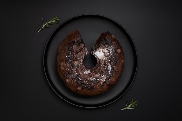 Donkere plaat met een chocoladecake op een zwarte achtergrond