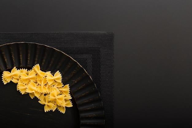 Donkere plaat met pasta op een donkere doek