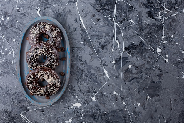 Donkere plaat van chocolade donuts met kokos hagelslag op marmer.