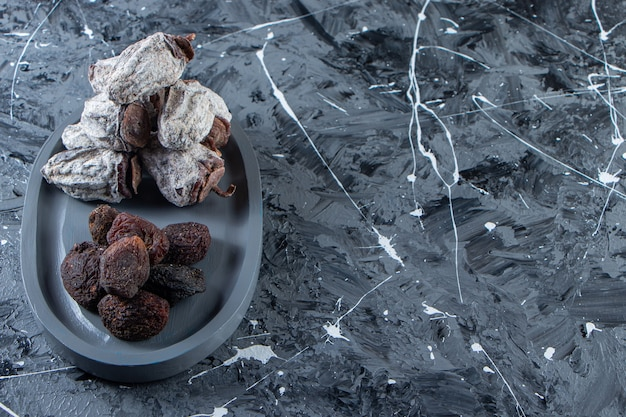 Donkere plaat van gedroogde smakelijke kaki en dadels op marmeren achtergrond.