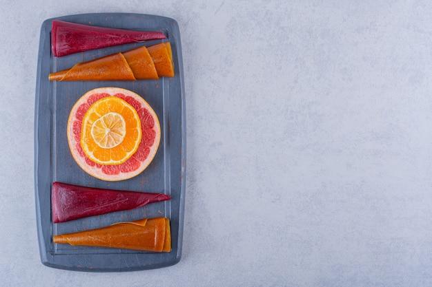 Donkere plaat van heerlijke droge fruitpulp en grapefruit op steen.