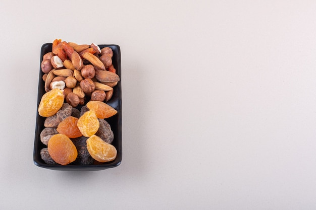 Donkere plaat van verschillende biologische noten op witte achtergrond. hoge kwaliteit foto