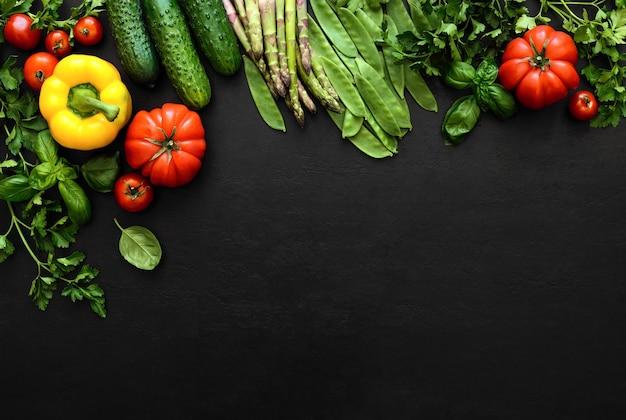 Donkere platliggende culinaire achtergrond met verse producten, uitzicht van bovenaf, lege ruimte voor een tekst