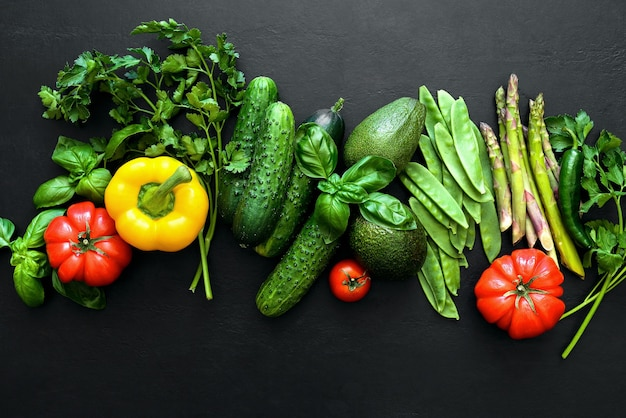 Donkere platliggende culinaire achtergrond met verse producten, uitzicht van bovenaf