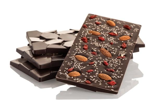 Donkere rauwe chocolade met amandelen en gojibessen op een witte achtergrond. isoleren