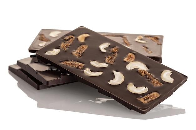 Donkere rauwe chocolade met cashewnoten en gedroogde vijgen op een witte achtergrond. geïsoleerd