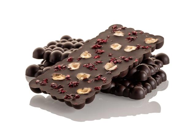 Donkere rauwe chocolade met haselnoot en gevriesdroogde kersen op een witte achtergrond. isoleren