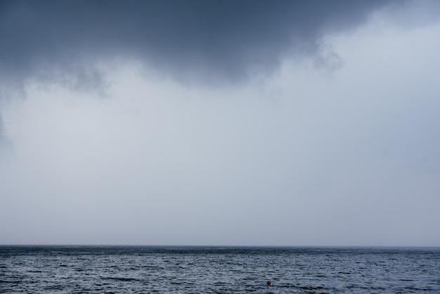 Donkere regenachtige wolken boven het landschap van het zeeoppervlak