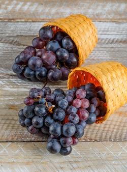 Donkere rode druiven in rieten manden hoge hoekmening op een houten achtergrond