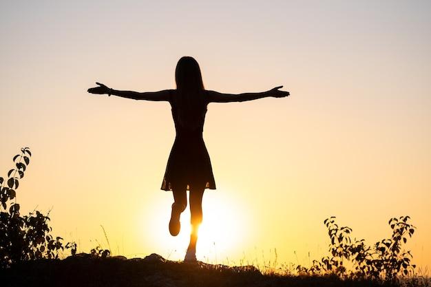 Donkere silhouet van een jonge vrouw met opgeheven handen op een steen genieten van de zonsondergang buiten in de zomer.
