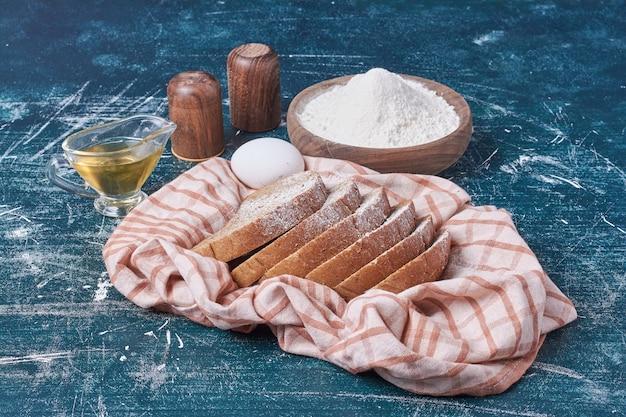 Donkere sneetjes brood met ingrediënten op blauwe tafel.