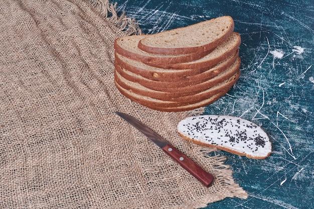 Donkere sneetjes brood met zure room op blauw.