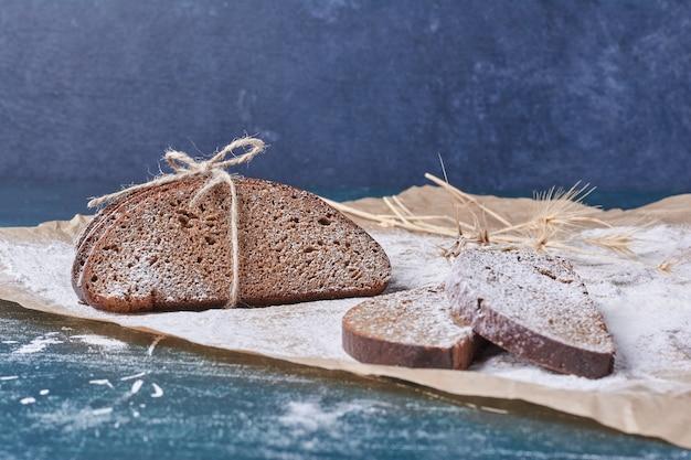 Donkere sneetjes brood op een houten bord op blauwe tafel.
