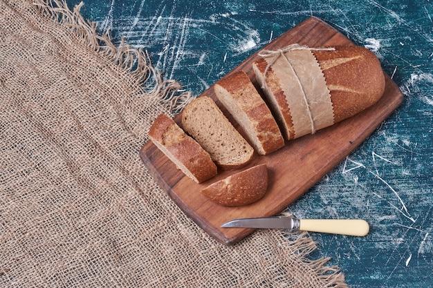 Donkere sneetjes brood op een houten bord.