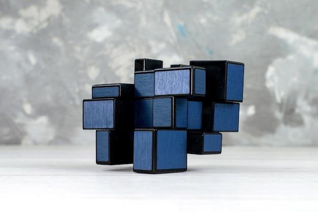 Donkere speelgoedconstructies ontworpen en gevormd op een lichte, plastic kubus van speelgoedrubberen