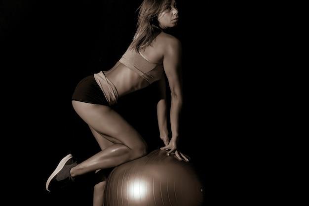 Donkere sport sexy meisje in sportkleding voert push-ups op grijze fitball in de sportschool.