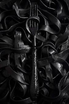 Donkere tagliatelledeegwaren met vork