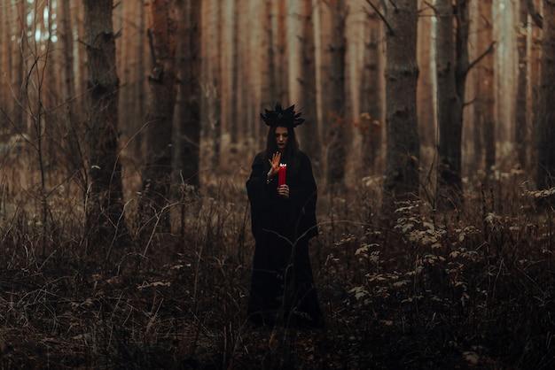 Donkere verschrikkelijke heks met kaarsen in haar handen voert een occult mystiek ritueel uit in het bos