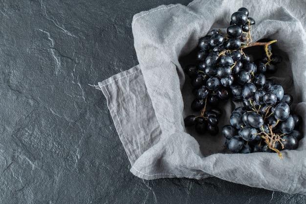 Donkere verse druif in mand op grijs tafellaken.