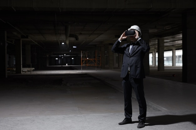 Donkere volledige lengte portret van zakenman vr-versnelling dragen op bouwplaats terwijl toekomstige project in 3d visualiseert,