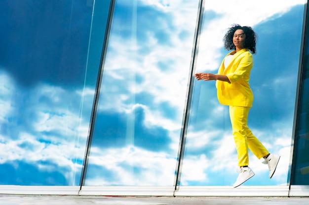 Donkere vrouw in een sprong, springend tegen een achtergrond van heldere hemel. mooie afro-amerikaanse zwarte zakenvrouw. ruimte kopiëren