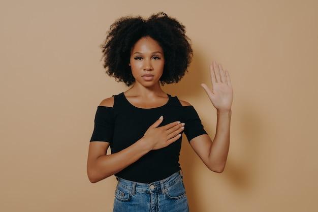 Donkere vrouw met een casual shirt en spijkerbroek die over een geïsoleerde beige achtergrond staat, vloekend poseert met de hand op de borst en de vingers omhoog, terwijl ze de eed van loyaliteit belooft. patriottisme concept