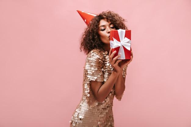 Donkere vrouw met pluizig haar in vakantiepet en glanzende stijlvolle kleding die haar geschenkdoos kust op roze geïsoleerde muur..