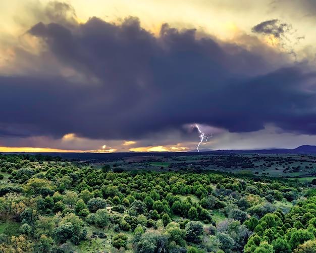 Donkere wolk stormstraal. dramatische regenachtige hemel over het boomgebied.
