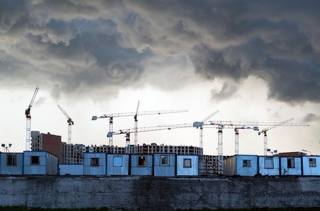 Donkere wolken boven de bouwplaats en bouwkranen.