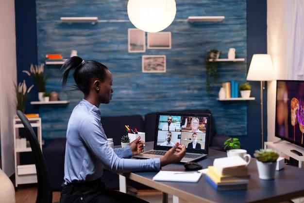 Donkere zakenvrouw die op afstand werkt en met collega's spreekt tijdens een videogesprek. met behulp van moderne technologie netwerk draadloos praten op virtuele vergadering overuren maken.