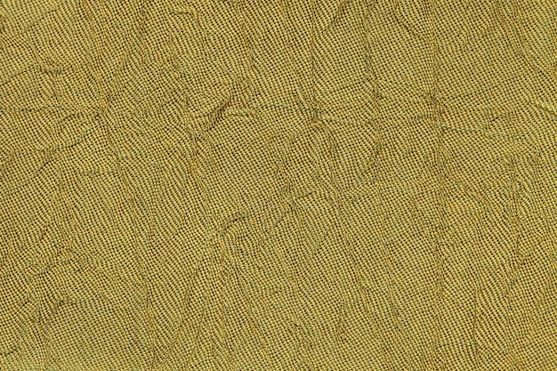 Donkergeel golvend textiel. stof met de close-up van de vouwentextuur.