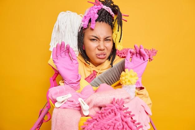 Donkergevild vrouwelijk model druk bezig met het schoonmaken van het huis, houdt de handen in handschoenen