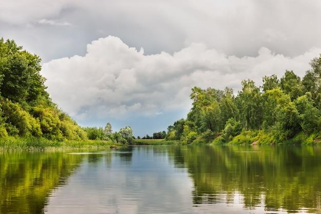 Donkergrijze cyaan bewolkte stormachtige lucht boven de rivier met reflecties op water. zomer landschap
