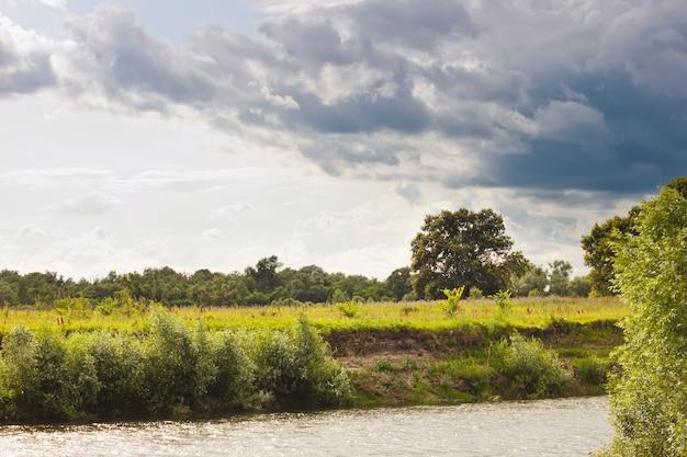 Donkergrijze cyaan bewolkte stormachtige lucht boven de rivier. zomer landschap