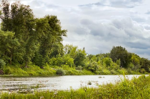 Donkergrijze cyaan bewolkte stormachtige lucht boven de rivier
