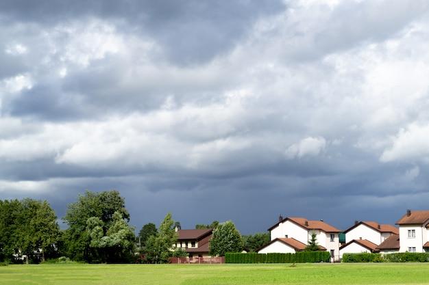 Donkergrijze dramatische wolken en leuke kleine huisjes