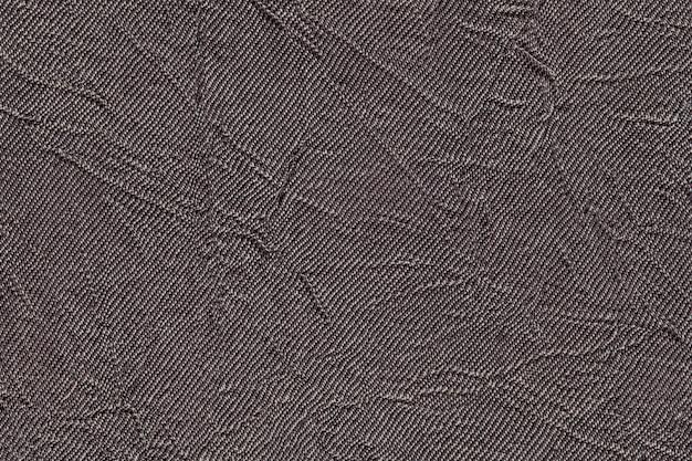 Donkergrijze golvende achtergrond van textiel. stof met de close-up van de vouwentextuur.