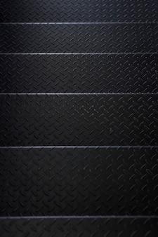 Donkergrijze stalen trap met ruitpatroon achtergrond