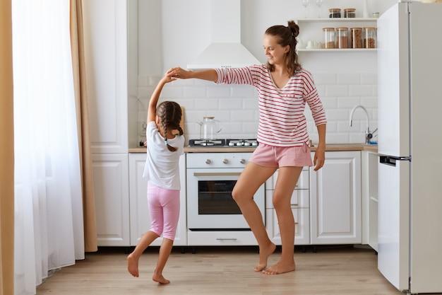 Donkerharig meisje dat met moeder danst, dochter die zich geweldig voelt dansen met haar liefhebbende moeder in de keuken, familie in casual stijl die samen plezier heeft.