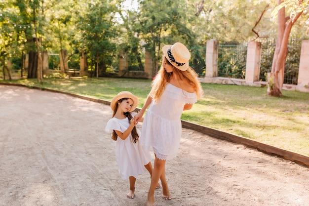 Donkerharig meisje dat moeder smeekt over iets dat haar op straat in de ogen kijkt. outdoor portret van slanke vrouw in schipper hand in hand met dochtertje.