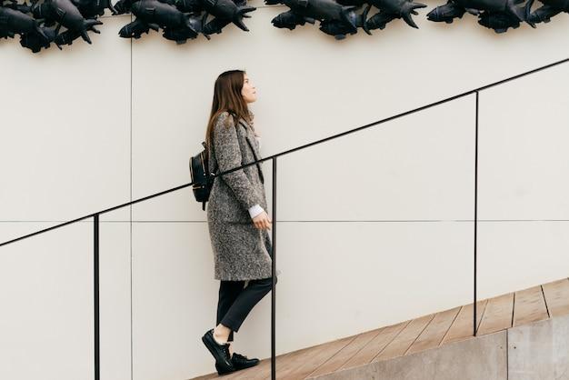 Donkerharig stadsmeisje in grijze jas klimt de trap op tegen de achtergrond van een ongewone muur, straatstijl