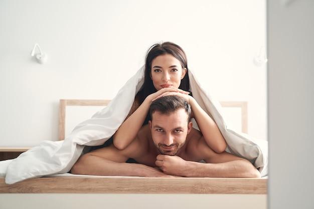 Donkerharige aantrekkelijke jonge vrouw onder de deken, leunend op het hoofd van haar echtgenoot met haar handen