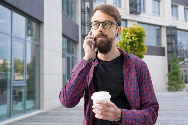 Donkerharige bebaarde man in bril praten via smartphone