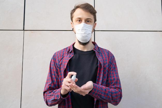 Donkerharige bebaarde man in masker met ontsmettingsmiddel op handen