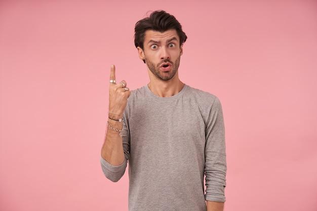 Donkerharige bebaarde man met verbaasd gezicht poseren, het dragen van grijze trui, kijken en wenkbrauwen optrekken, naar boven wijzend met wijsvinger