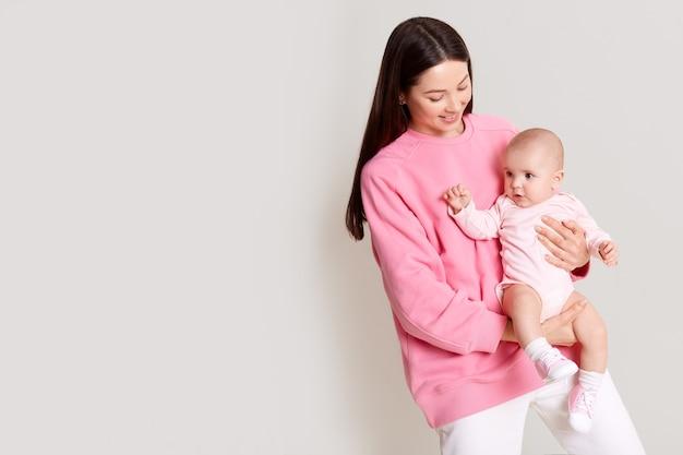 Donkerharige blanke moeder die baby in handen houdt en naar haar dochter kijkt, mooie vrouwelijke jurken roze sweatshirt met baby geïsoleerd over witte muur met kopie ruimte.