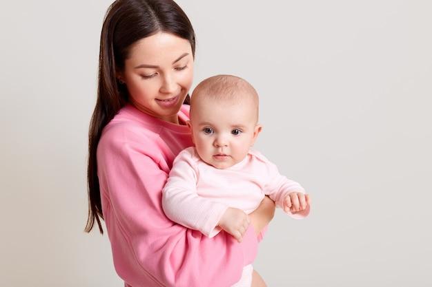 Donkerharige blanke moeder met lang donker haar die haar schattige babymeisje, gekleed in bodysuit, vrouw in casual outfit houdt die haar dochter met liefde bekijkt, geïsoleerd over witte muur.