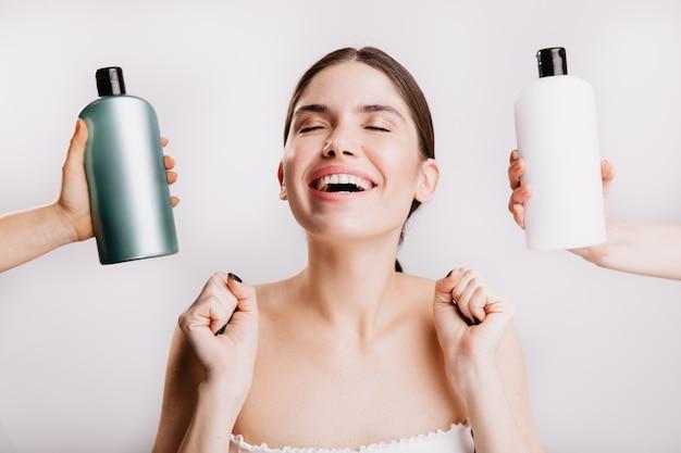 Donkerharige dame lacht vrolijk, poseren op geïsoleerde muur met flessen shampoos.